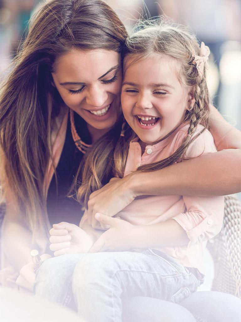 Eine Nanny sitzt lachend mit einem jungen Mädchen auf dem Schoß in einem Café in Berlin