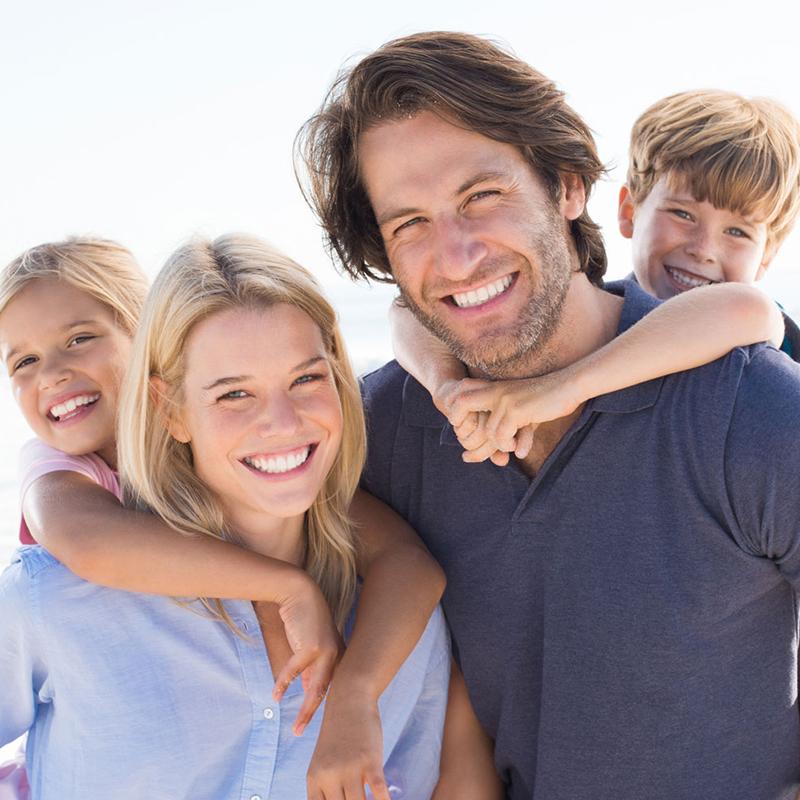 Mutter und Vater tragen ihre Kinder Huckepack und lachen