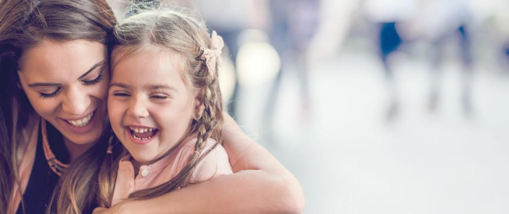 Eine Nanny sitzt lachend mit einem jungen Mädchen auf dem Schoß in einem Café in München