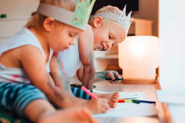 Zwei Kinder sitzen am Boden und malen mit Buntstiften während einem Babysitter Kurs